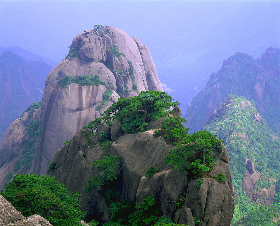 A Rocky Outcropping Overlooks A Mist-covered China Mountain Range Photograph by Rubberball