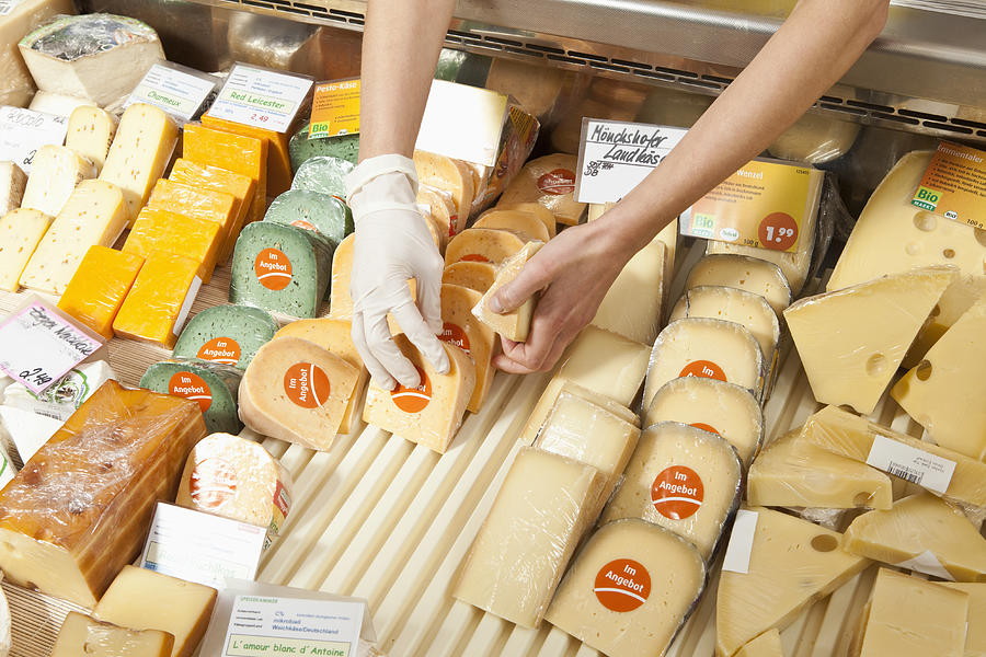 A sale clerk in a cheese shop, focus on hands Photograph by Antenna