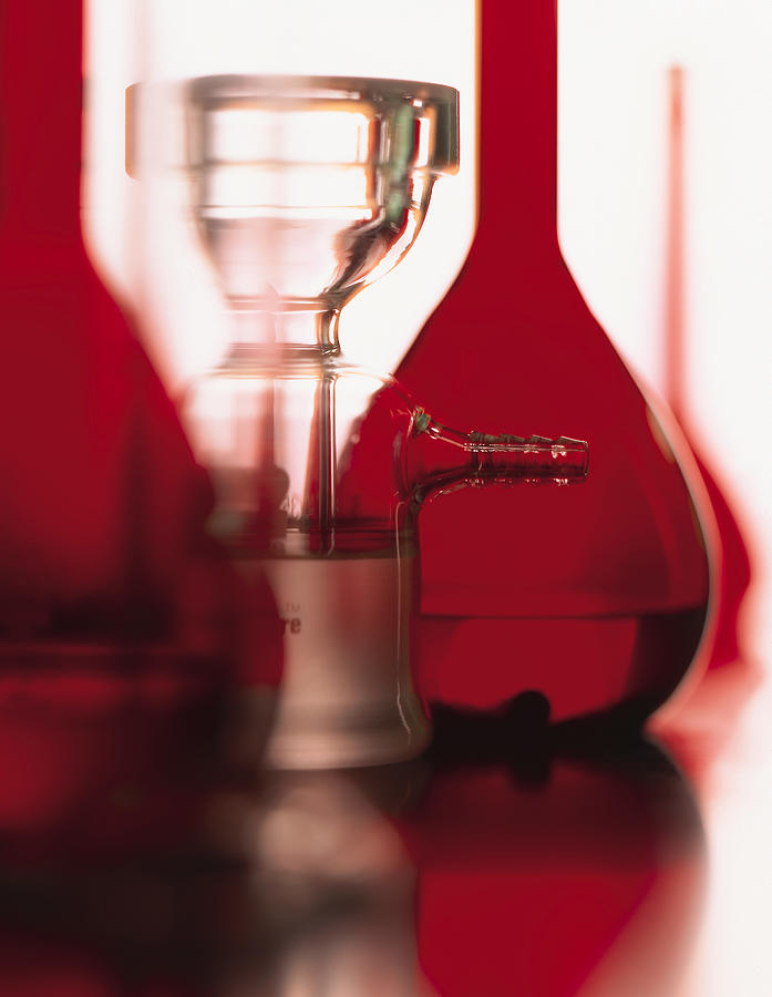 A Series Of Red Flasks And Beakers Stand On A Shiny Table With A White Background Photograph by Photodisc