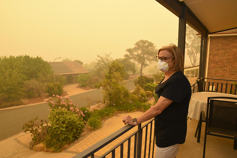 A woman, on a balcony, wears a face mask to protect herself against very dangerous level of air pollution.  A thick yellow fog coming from the nearby forest fires covers Canberra city. Photograph by Daniiielc