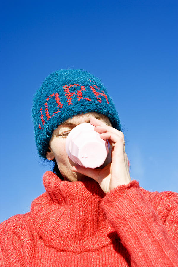 A woman with a blue hat drinking from a cup Sweden. Photograph by Ulf Huett Nilsson