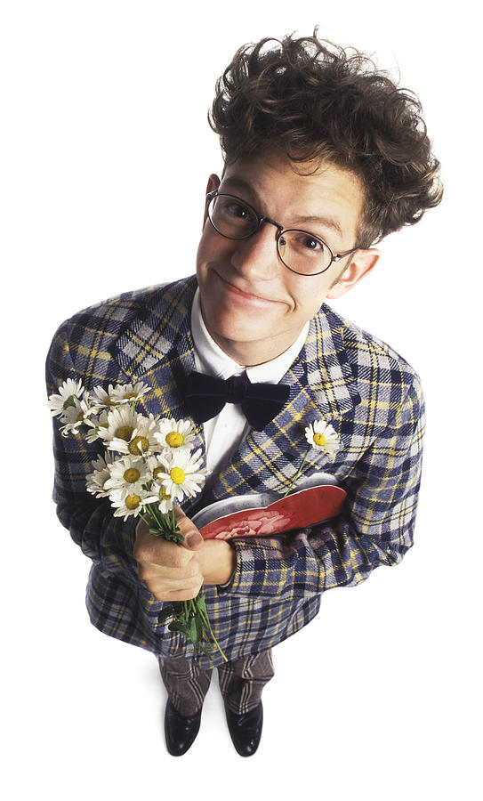 A Young Adult Male Nerd In A Plaid Suit With Flowers And Chocolates Smiles Up At The Camera Photograph by Photodisc