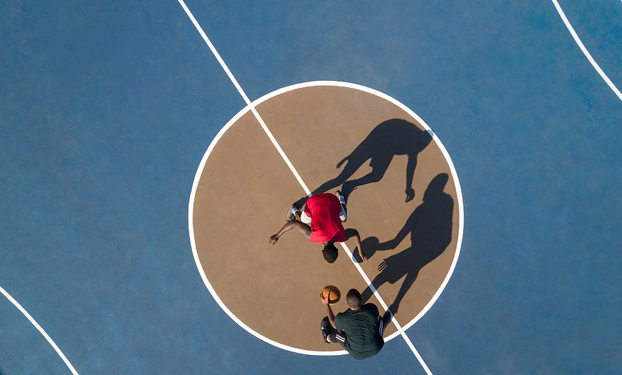 Aerial shot of 2 basketball players and shadows Photograph by Hello Africa