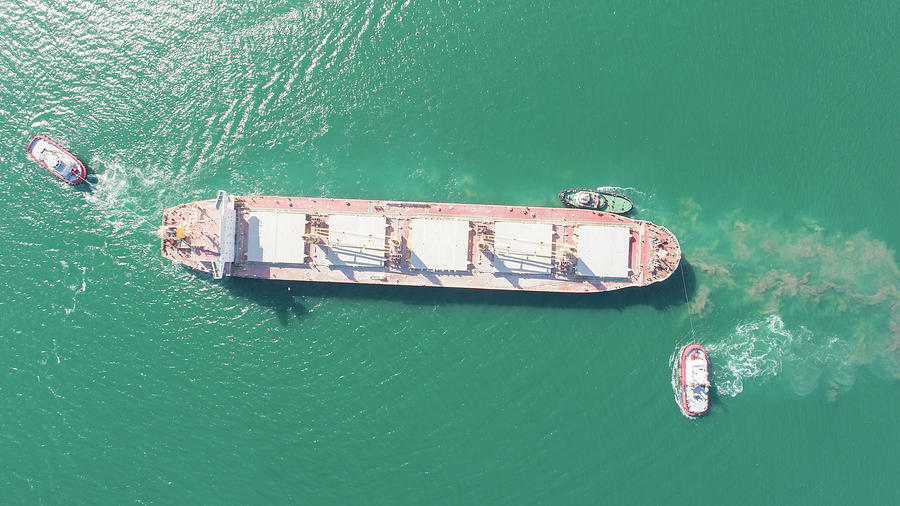 Aerial Top Down View Of Tug Boats Assisting Big Cargo Ship. Large Cargo Ship Enters The Port Escorted By Tugboats. Photograph