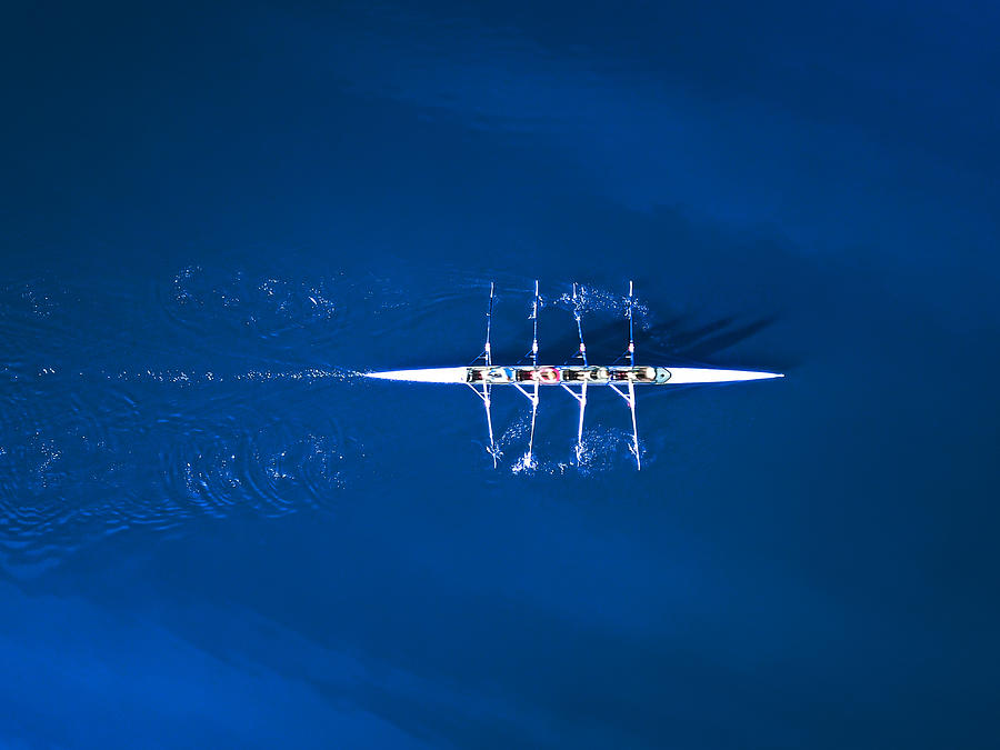 Aerial view of a rowing boat surrounded by classic blue water Photograph by Felix Cesare
