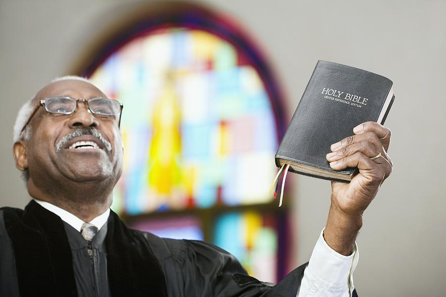 African American Reverend holding up Bible Photograph by Hill Street Studios