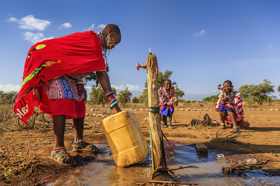 African woman from Maasai tribe collecting water, Kenya, East Africa Photograph by Hadynyah