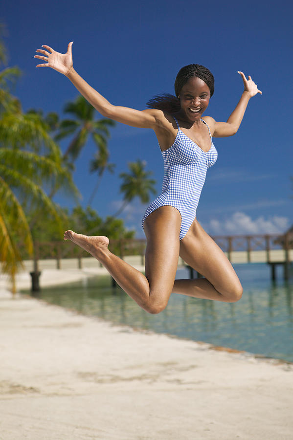 An Attractive African American Woman In A Swimsuit Jumps Up Into The Air Wildly At The Beach Photograph by Photodisc