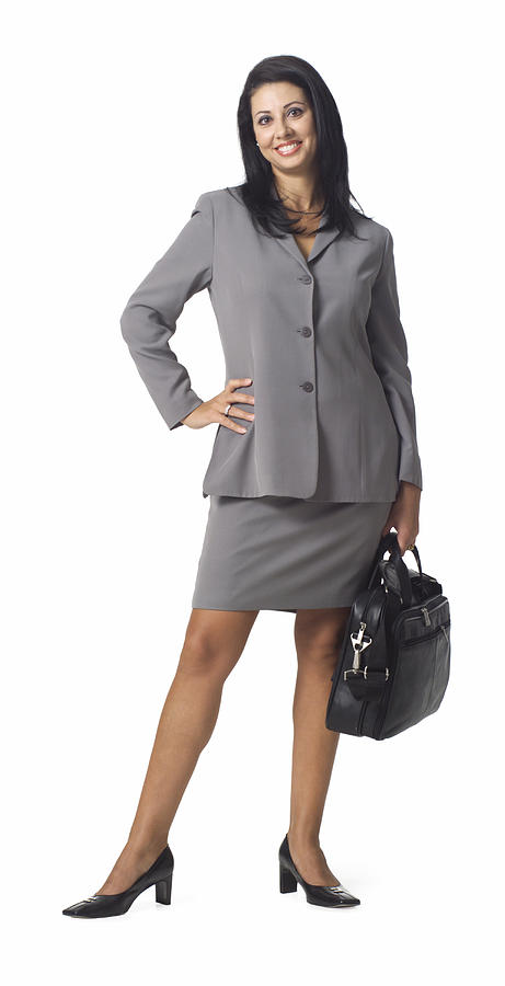 An Ethnic Business Woman In A Grey Suit Holds Her Computer Bag And Smiles Photograph by Photodisc