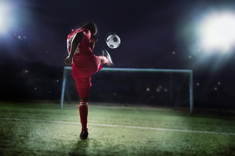 Athlete kicking soccer ball into a goal Photograph by FangXiaNuo