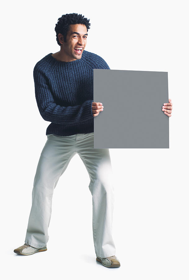 Attractive African American Man Wears Khaki Pants Grey Sweater Holds Blank Sign Smiles Enthusiasm Photograph by Photodisc
