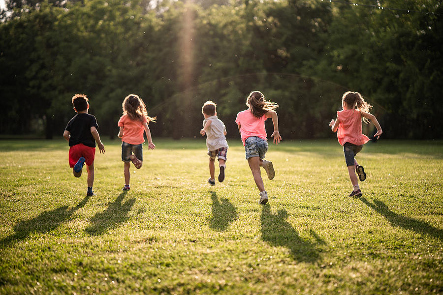 Back view group of children running in nature Photograph by StockPlanets