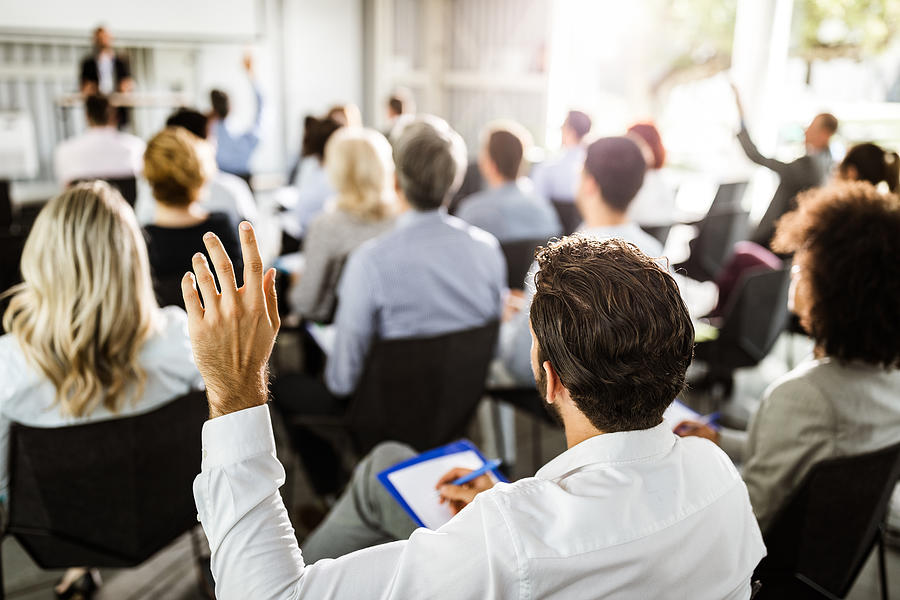 Back view of a businessman raising his hand on a seminar. Photograph by Skynesher