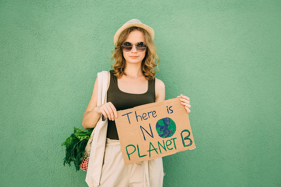 Beautiful blonde girl holding THERE IS NO PLANET B over green background Photograph by Iuliia Bondar