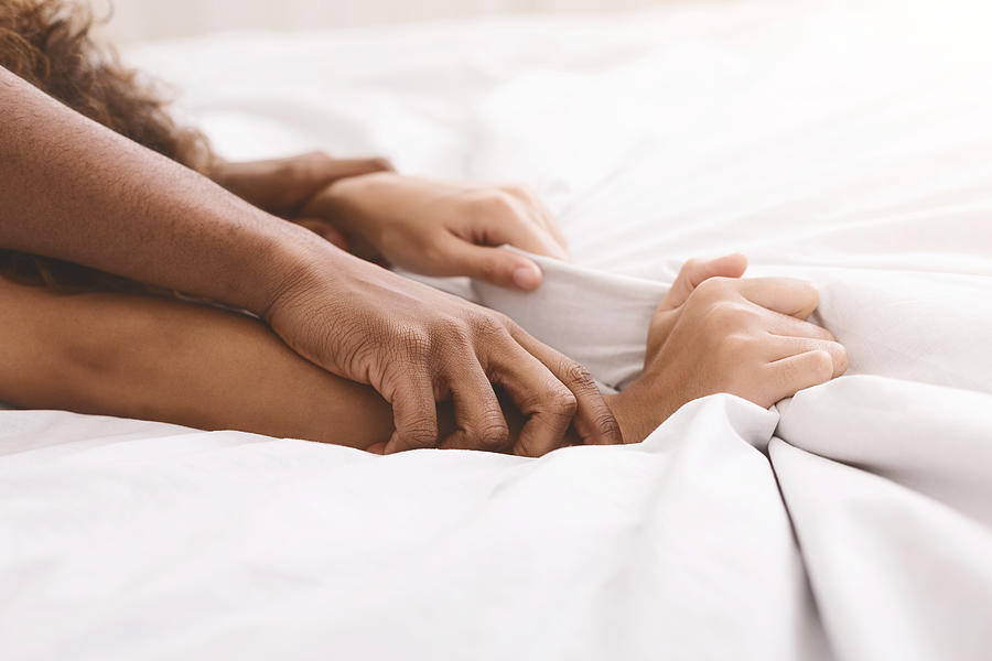 Black couple hands pulling white sheets in ecstasy Photograph by Prostock-Studio