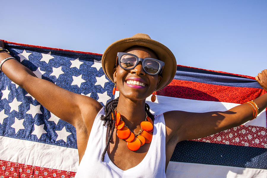 Black woman holding American flag under blue sky Photograph by Adam Hester