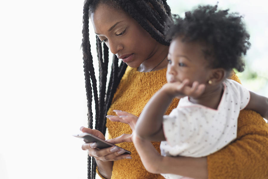 Black woman holding baby daughter using cell phone Photograph by JGI/Tom Grill