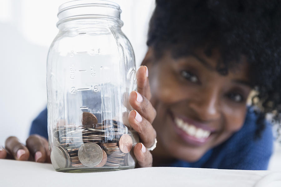 Black woman saving coins in jar Photograph by JGI/Jamie Grill