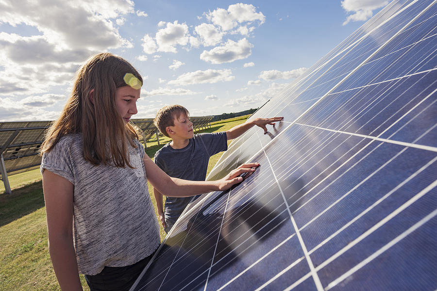 Boy And Girl Standing Next To Solar Panels Photograph by Johner Images
