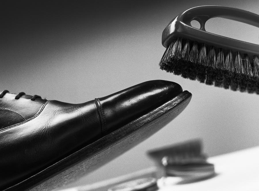 Brush above leather shoe, close-up, b&w Photograph by Christian Zachariasen