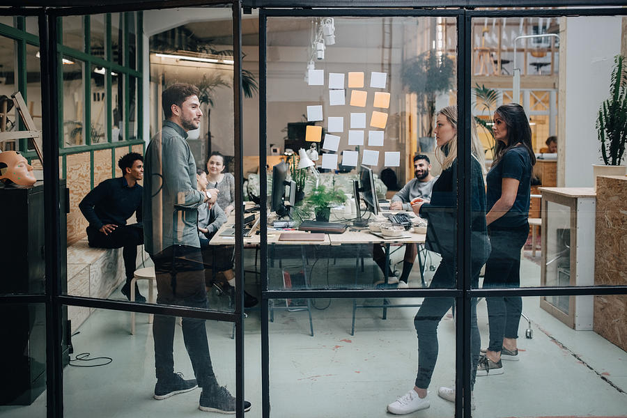 Business colleagues brainstorming in meeting at office seen through glass wall Photograph by Maskot