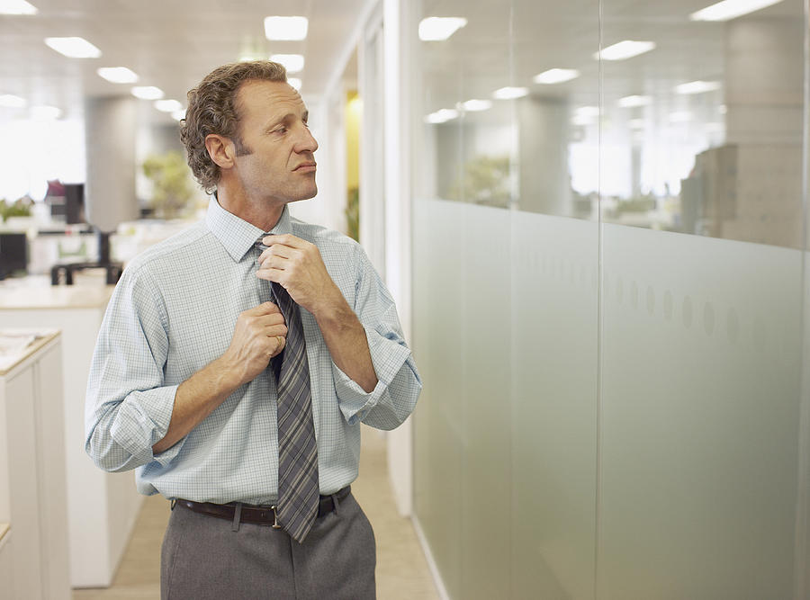 Businessman adjusting tie in office Photograph by Paul Bradbury