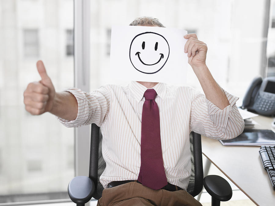 Businessman holding picture of happy face Photograph by Robert Daly
