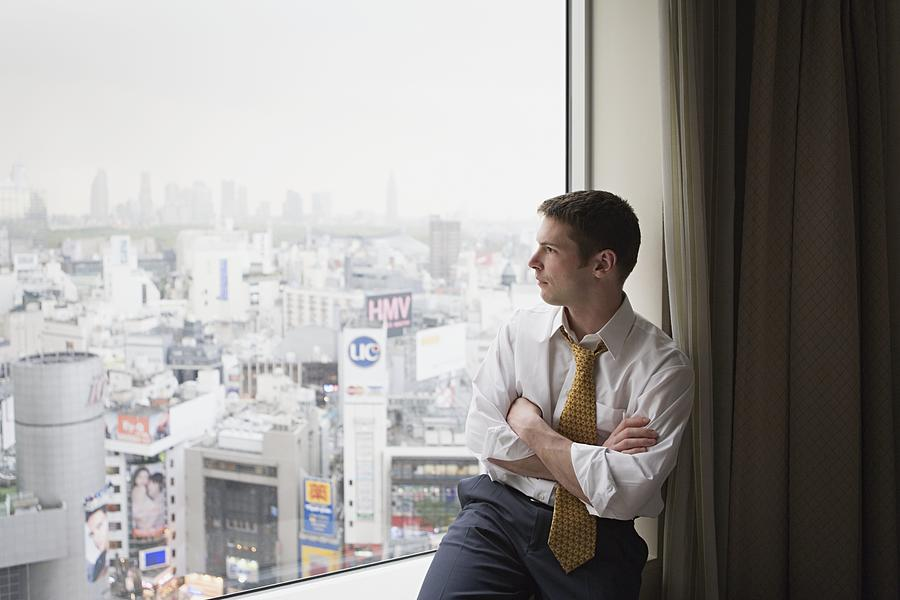 Businessman looking out of window Photograph by Image Source
