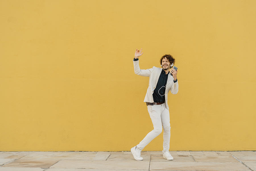 Businessman singing and dancing in front of yellow wall listening music with headphones and smartphone Photograph by Westend61