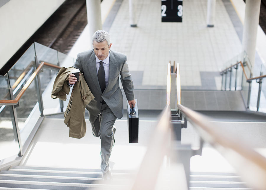 Businessman walking up stairs in train station Photograph by Paul Bradbury