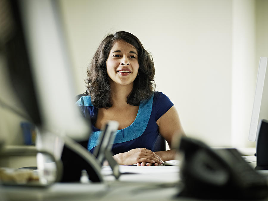 Businesswoman in discussion in office smiling Photograph by Thomas Barwick