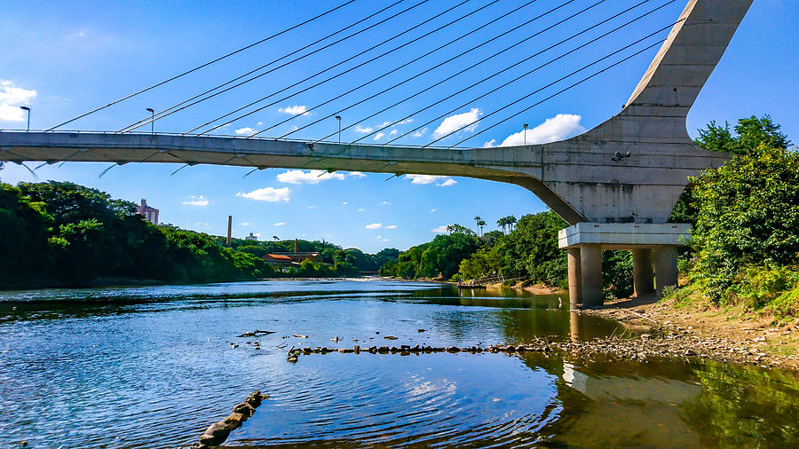 Cable-stayed bridge over the Piracicaba River in a dry season, under blue sky between clouds. Photograph by CRMacedonio