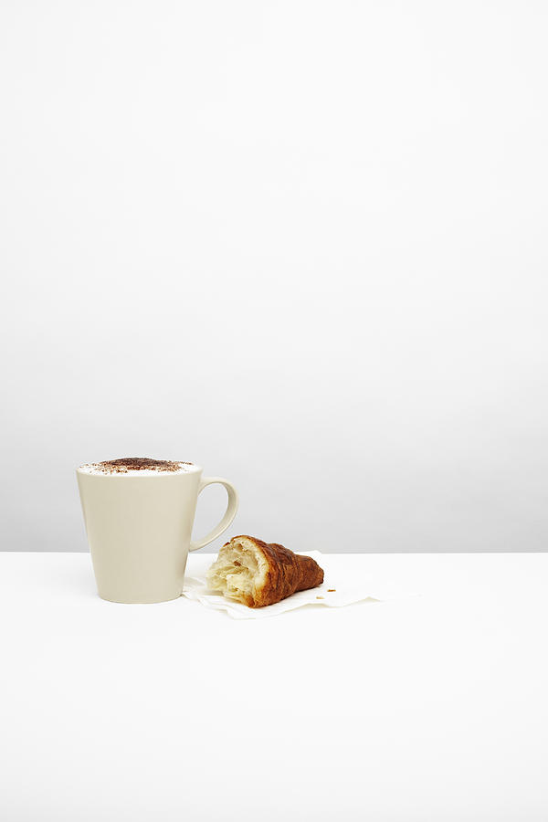 Cappuccino with croissant on table Photograph by Microzoa Limited