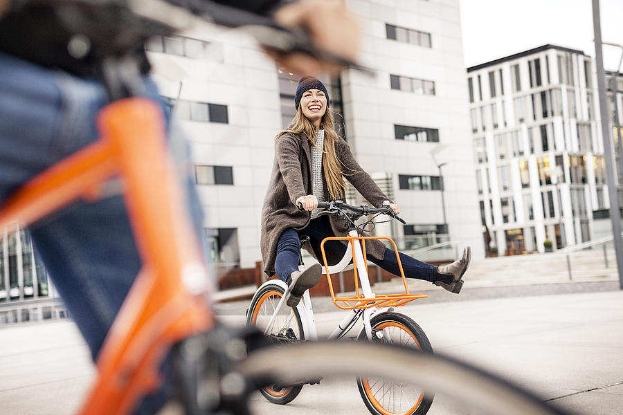 Carefree woman with man riding bicycle in the city Photograph by Westend61