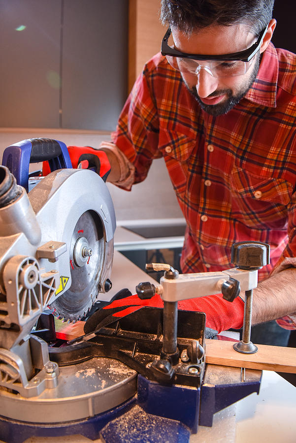 Carpenter use electric saw to cutting wooden plank Photograph by Dragan Smiljkovic