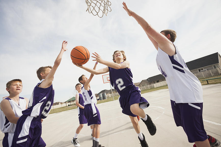 Caucasian boys playing basketball on court Photograph by Mike Kemp