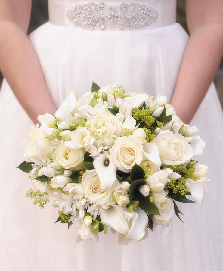 Caucasian bride holding bouquet of white flowers Photograph by Jacobs Stock Photography Ltd