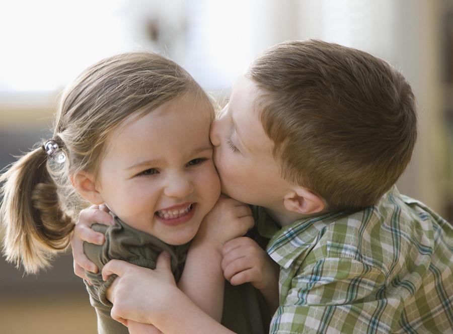 Caucasian brother kissing sister Photograph by Jose Luis Pelaez Inc