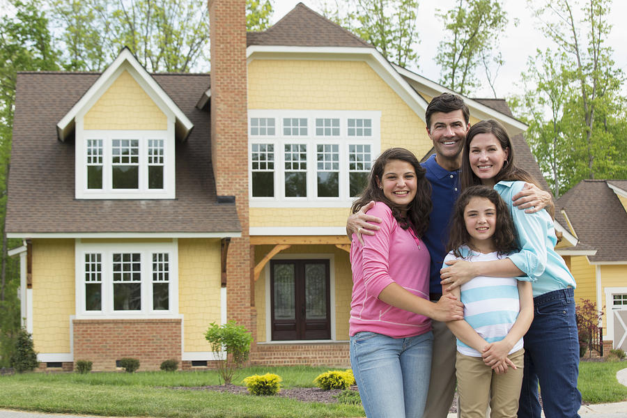 Caucasian family smiling outside house Photograph by Ariel Skelley