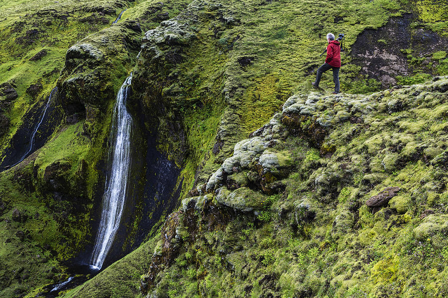 Caucasian hiker admiring waterfall and rock formations on mountainside Photograph by Jeremy Woodhouse