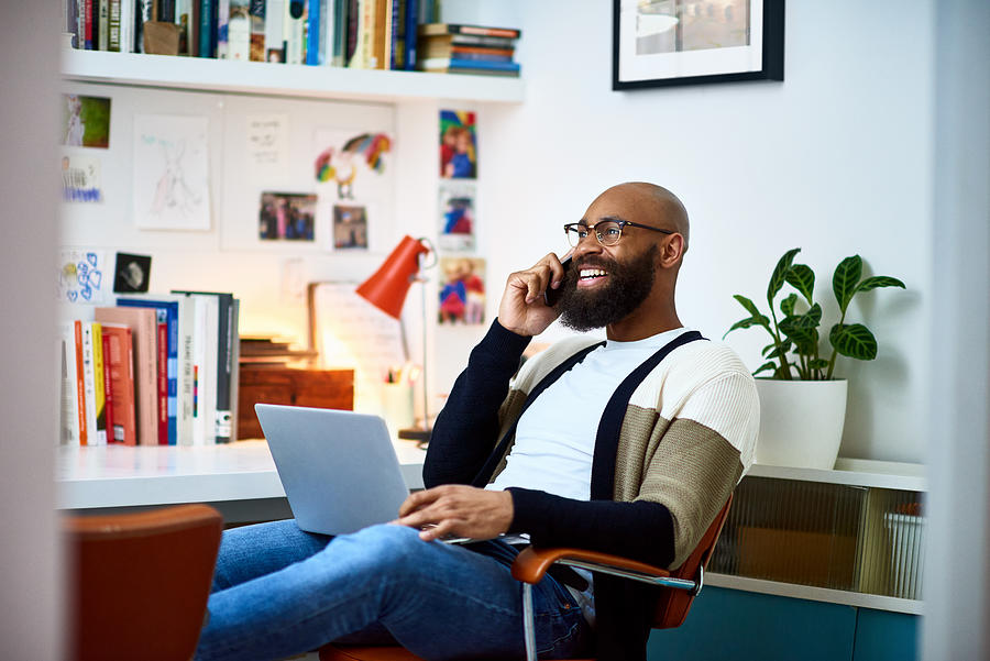Cheerful businessman working from home on phone Photograph by 10000 Hours