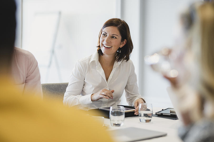 Cheerful mid adult woman smiling at business meeting Photograph by SolStock