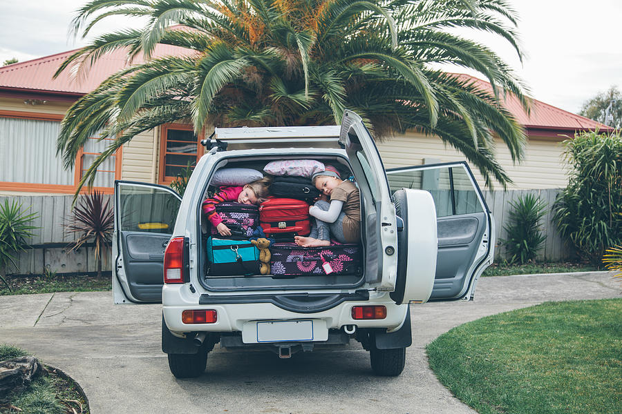 Children squashed into back of car with luggage Photograph by Jodie Griggs
