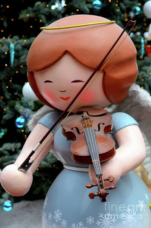 Christmas angel statue with wings in blue dress plays violin with bow by Imran Ahmed