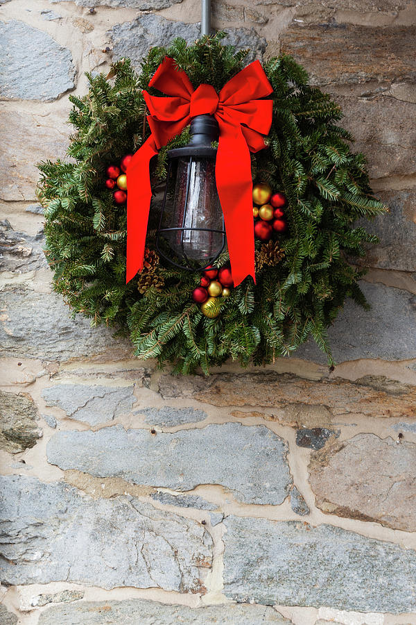 Christmas Wreath With Red Bow Against Stone Wall Photograph
