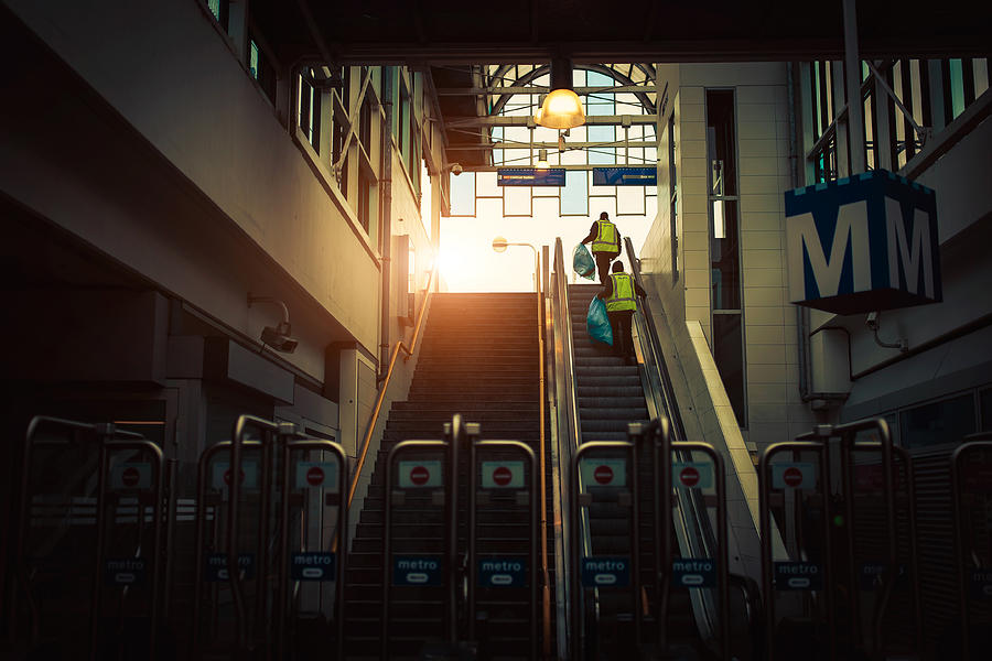 Cleaning workers walking up the stairs in a metro/subway underground station. Sunlight at the end, in a cinematic scene. Photograph by Photo by Jeff Krol