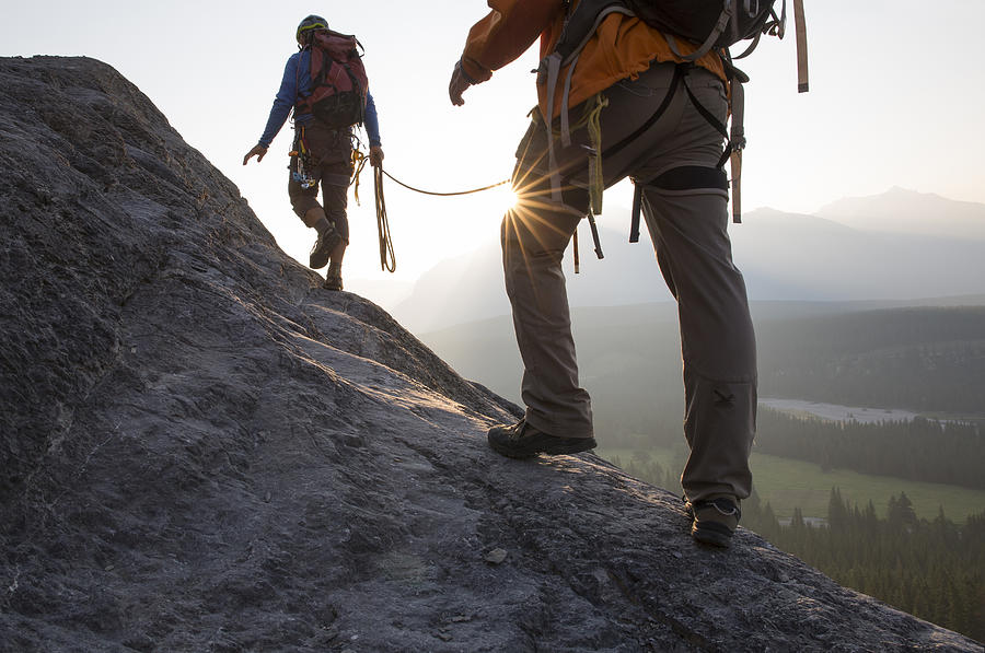 Climbers ascend mountain ridge, sunrise Photograph by Ascent Xmedia