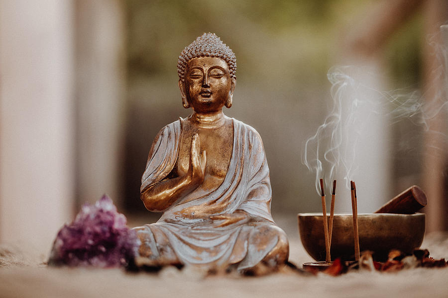 Close up of a Buddha figurine and smoky incense with gong and amethyst Photograph by DianaHirsch