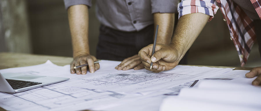 Close up of two people reviewing building blueprints Photograph by Vm