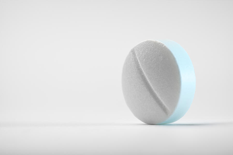 Close-up shot of a round pill on white background Photograph by NoSystem images